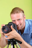 Handsome photographer with camera and tripod, on green background — Stock Photo