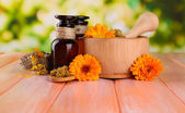 Medicine bottles and calendula flowers on wooden table — Stock Photo