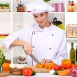 Young woman chef cooking in kitchen — Stock Photo