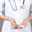 Close-up of female doctor hand holding pills, on color background — Stock Photo #27236633