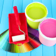 Set for painting: paint pots, paint-roller on blue wooden table — Stock Photo #27237281