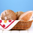 Composition with bread and rolls on wooden table, on color background — Stock Photo #27238007