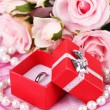 Rose and engagement ring on pink cloth — Stock Photo #27238957