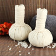 Herbal compress balls for spa treatment and towel on bamboo background — Stock Photo #27239803