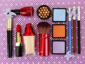 Decorative cosmetics on purple background — Stock Photo