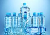 Diferentes botellas de agua en el fondo azul — Foto de Stock