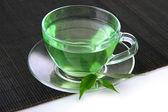 şeffaf bardak yeşil çay bambu mat, üzerinde beyaz izole — Stok fotoğraf