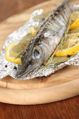 Fish in foil with herbs and lemon on board on wooden table close-up — Stock Photo