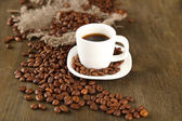Cup of coffee and coffee beans on wooden background — Stock Photo