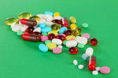 Assortment of pills, tablets and capsules on green background — Stock Photo