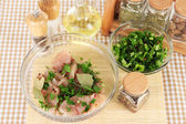 Chicken meat in glass bowl,herbs and spices on checkered napkin close-up — Stock Photo