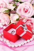 Rose och förlovningsring på rosa tyg — Stockfoto