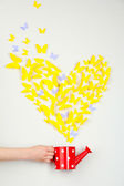 Paper yellow butterfly in form of heart fly out watering can — Stock Photo