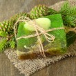 Hand-made soap and green pine cones on wooden background — Stock fotografie