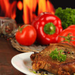 Stock Photo: Piece of fried meat on plate on wooden table on fire background
