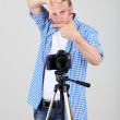 Handsome photographer with camera on tripod, on gray background — Stock Photo