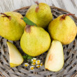 Pears on braided tray on wooden table — Stock Photo #27244643