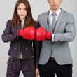 Young business in boxing gloves on grey background — Stock Photo #27246381