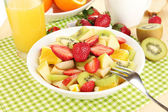 Useful fruit salad of fresh fruits and berries in bowl on napkin on wooden table close-up — Stock Photo