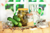 Tasty fresh and canned cucumbers, on wooden table on bright background — Stock Photo