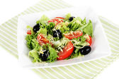 Light salad on plate on napkin isolated on white — Stock Photo