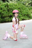 Little girl in roller skates at park — Stok fotoğraf