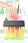 Hand putting paper into shredder machine, on office interior background — Stock Photo