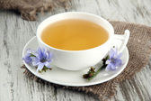 Cup of tea with chicory, on wooden background — Stock Photo