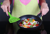 Hands cooking vegetable ragout in pan on gray background — Stock Photo