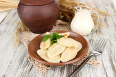 Tasty dumplings with fried onion on brown plate, on wooden background — Stock Photo