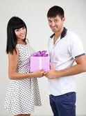 Beautiful loving couple with gift on grey background — Stock Photo