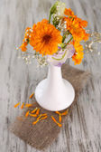 Calendula flowers in vase on wooden background — Stock Photo