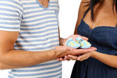 Young married couple with baby clothes isolated on white — Stock Photo
