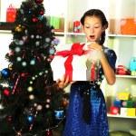 Little girl holding gift box near Christmas tree — Stock Photo #27316153