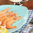 Shrimps with lemon on plate on wooden table close-up — Lizenzfreies Foto