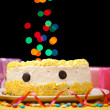 Happy birthday cake and gifts, on black background — Stock Photo