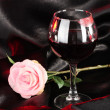 Glass of wine with lipstick imprint on black satin background — Stock Photo