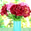 Stock Photo: Beautiful peonies in vase on table on bright background