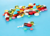 Assortment of pills, tablets and capsules on blue background — Fotografia Stock
