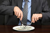 Young businessman having dinner dollars on black background — Stock Photo