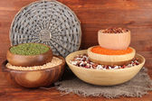 Different kinds of beans in bowls on wooden background — Stock Photo