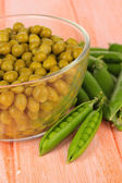Green peas on wooden background — Stock Photo