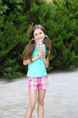 Niña en patines comiendo sabroso helado en el parque — Foto de Stock