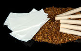 Tobacco and cigarette tubes, isolated on black — Stock Photo