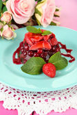 Tasty jelly dessert with fresh berries, on pink roses background — Stock Photo