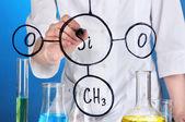химик женщина, написание формул на стекле на синем фоне — Стоковое фото