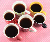 Many cups of coffee on pink napkin — Stock Photo