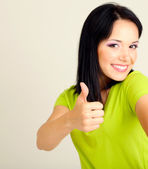 Happy young woman showing thumb up sign on grey background — Stock Photo
