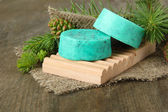 Hand-made soap and green pine cones on wooden background — ストック写真