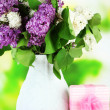 Beautiful lilac flowers, on wooden table on bright  background — Stock Photo